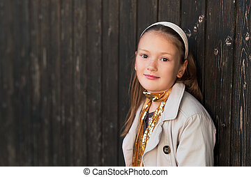 Outdoor portrait of a cute little girl wearing trench coat...