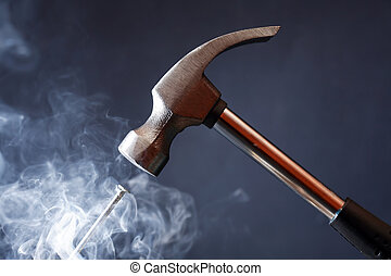 Hot Work Concept - Work tool. Metal hammer above nail with...