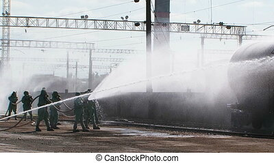 Group Of Firefighters Watering Tank At Railway Station - Two...