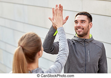 happy couple giving high five outdoors - fitness, sport,...