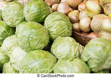 close up of cabbage and onion at street market - sale,...