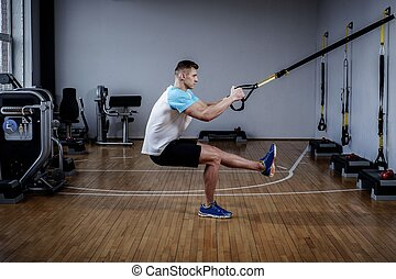 Attractive man during workout with suspension straps In The...