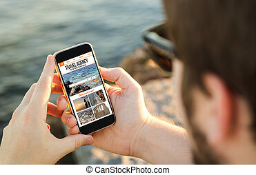 Man using his mobile phone on the coast to travel online