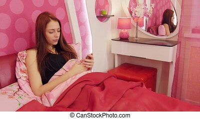 Woman with menstrual pain laying in pink bed - Young woman...