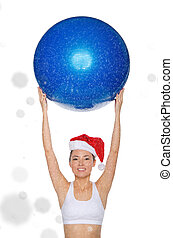 smiley asian woman in Santa cap holds fitball under snow...