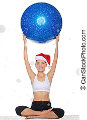 smiling asian woman in christmas cap holds pilates balls...