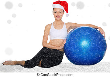 happy asian woman in christmas cap with fitball under snow...