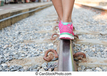 Woman walking on railroad tracks
