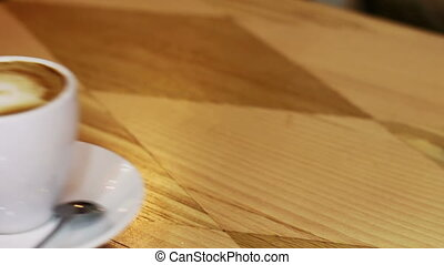 Coffee cup on wooden table - White cup of coffee with foam...