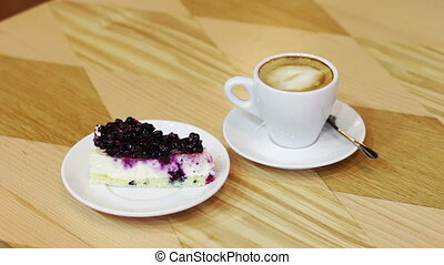 Cup of hot coffee and cheesecake with currant on a wooden...