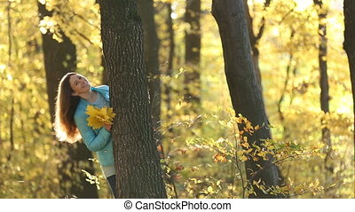 Girl hiding behind a tree in the autumn forest