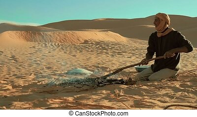 a man camping in the sahara desert - sahara man preparing...