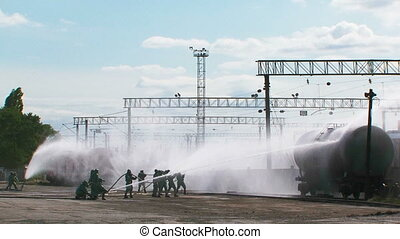 Group Of Rescuers Extinguishing Cistern At Railway Station -...