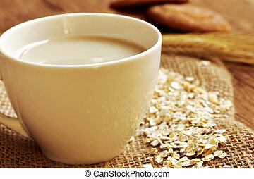 oat milk and rolled oats - closeup of a cup with oat milk...