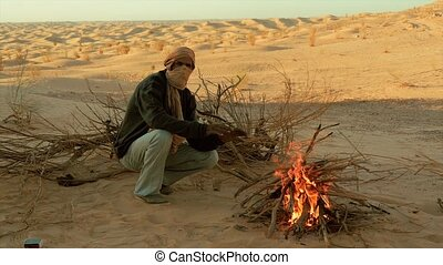 sahara man near a fire - a man camping in the sahara desert