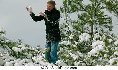 Young Couple Playing Snowball Fight In Snowy Pine Park -...