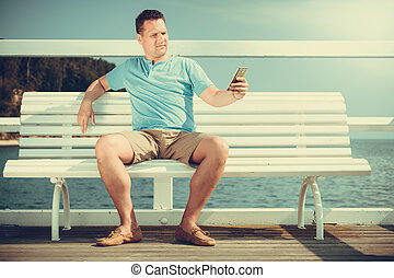 Man tourist on pier using smartphone Technology - Handsome...