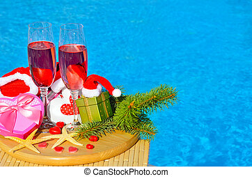Glasses with red champagne and Christmas decor on swimming...