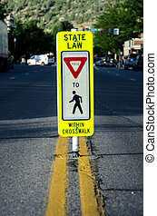 Yield in Cross Walk Sign - A stop sign reminders drivers in...