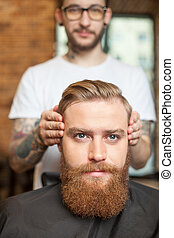 Skillful male barber is serving his client - Cheerful young...