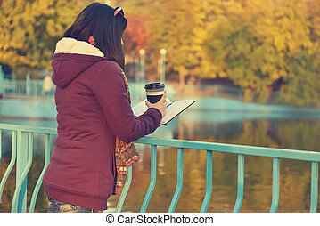 Girl reading a book - Girl with coffee cup and reading a...