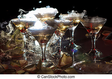 drink in glasses with the effect of dry ice on black...