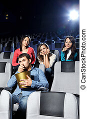 Enamoured girls admire the attractive man at cinema