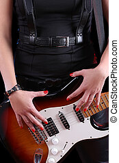 female hand on the detail of a guitar in dark back. Rock...