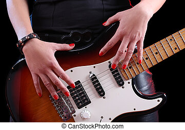 female hand on the detail of a guitar in dark back Rock star...