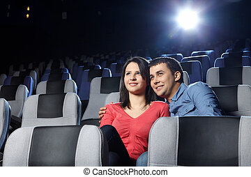 Embracing couple - Happy enamoured at a cinema look a film