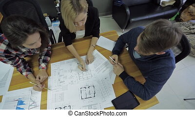 a group of architects discussing with the customer the customer blueprint project and the amount of work commissioned for the building, at the office, contract