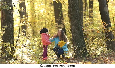 Mom and daughter with yellow leaves in hands
