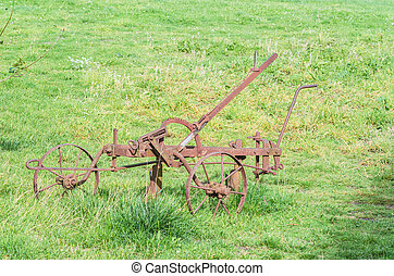 Old historical plow - Old historical rusty plow on a farm in...