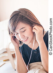 Cheerful young woman listening music - Cheerful young woman...