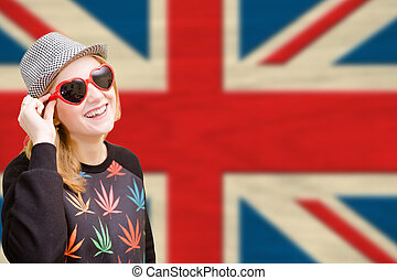 Pretty young woman in sunglasses on english union jack...