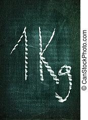 a kilogram written with a chalk on a blackboard
