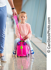 Adorable little girl at airport sitting on suitcase waiting for boarding