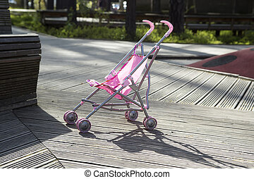 Pink pram stands alone in the park - Pink pram stands alone...