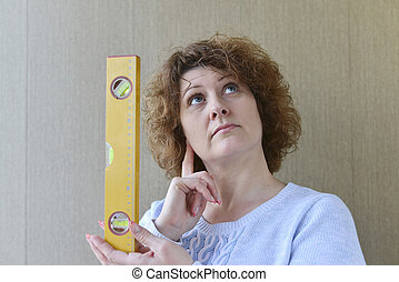 woman is holding construction tools - A woman is holding a...
