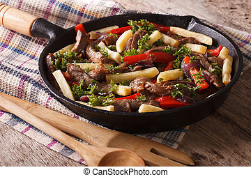 Homemade Peruvian cuisine: lomo saltado in a pan close-up...