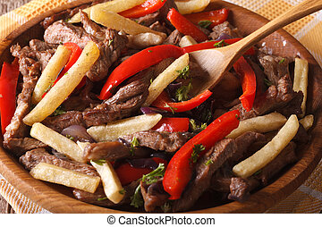 Peruvian cuisine: Lomo saltado close-up on a plate....