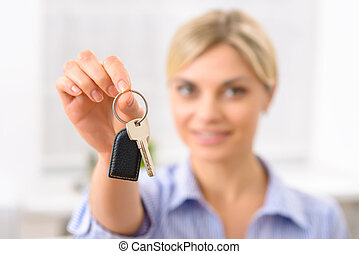 Young woman upholding room key - This is your room key...
