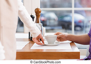 Waitress serving a cup pf coffee. - Freshly-made coffee....