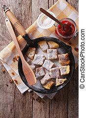 Kaiserschmarrn with plum sauce on a pan vertical top view -...