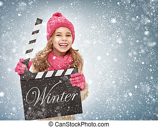 girl holding clapper board - child girl in winter clothes...