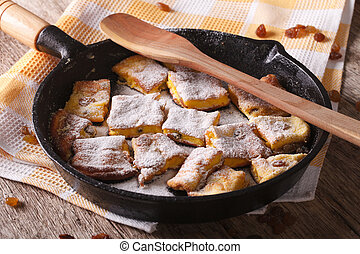 Delicious omelette Kaiserschmarrn close-up in a pan...