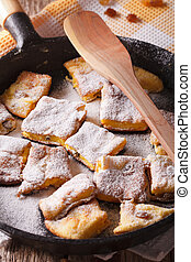 Delicious omelette Kaiserschmarrn close-up in a pan vertical...