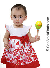 cute little girl playing with rattle in studio