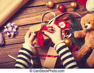 Female hands and christmas gift - Female hands are wrapping...