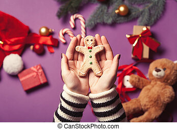hands are holding gingerbread man cookie - Female hands are...